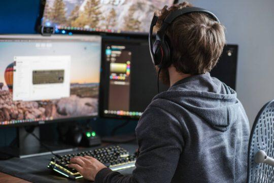 Persoon achter de computer, aan het spelen via het internet.